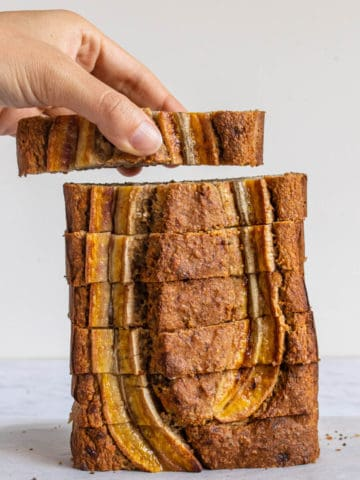 One piece of Healthy Banana Bread being picked up from a stack