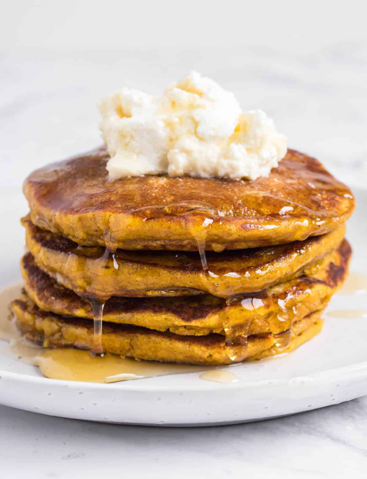 Pumpkin pancakes topped with ricotta and syrup
