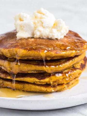 Pumpkin Pancakes topped with ricotta and drizzled with syrup