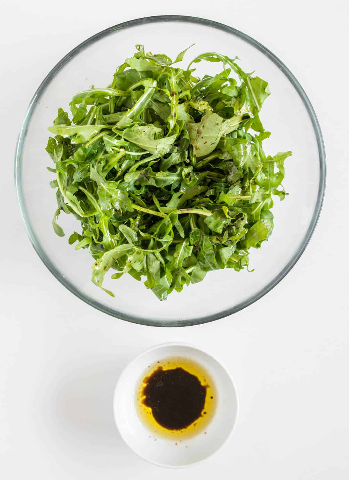 Rocket salad mixed with dressing in a bowl with small bowl of additional dressing