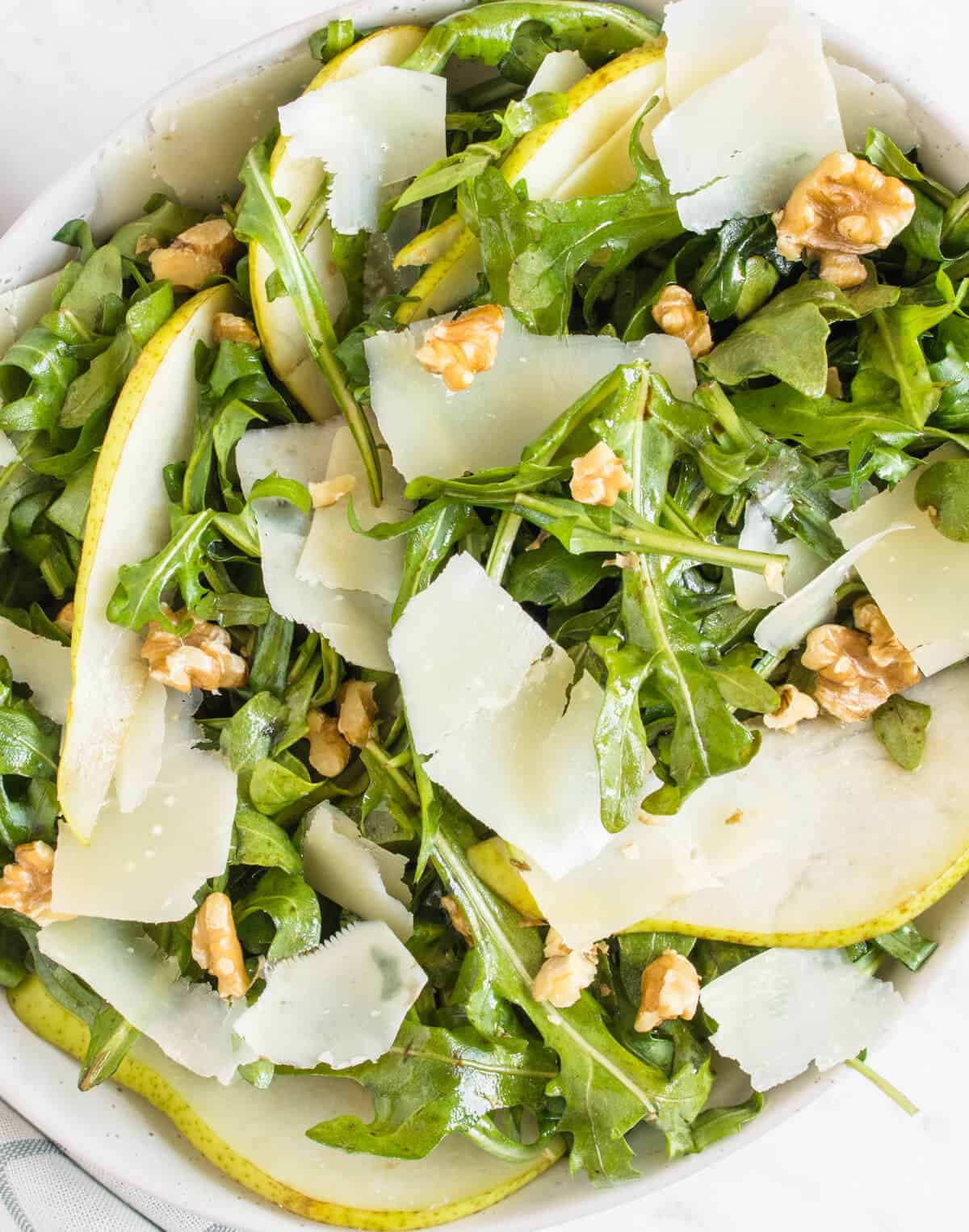 Close up shot of the rocket, pear and parmesan salad served in a bowl