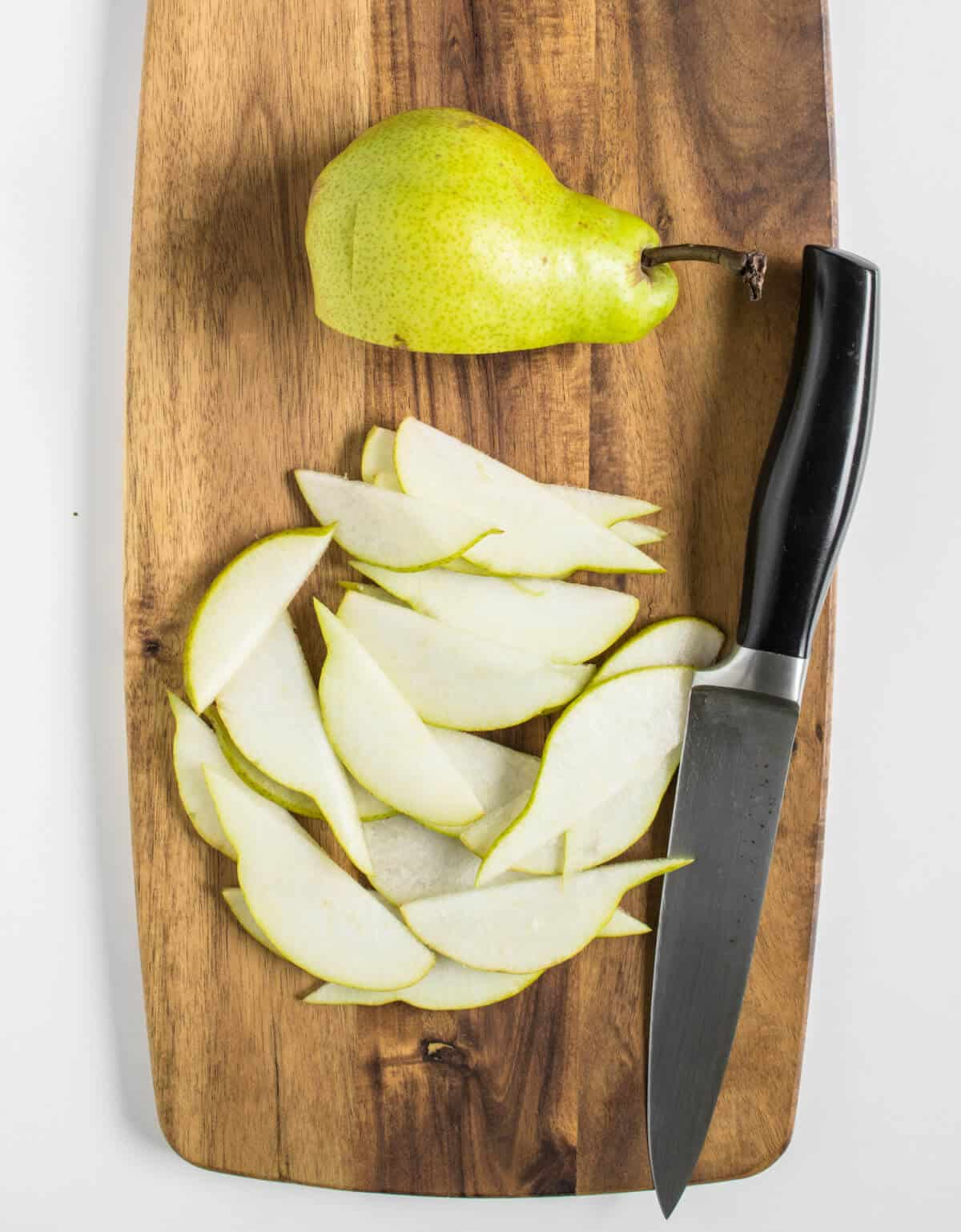 Pear being sliced thinly on a chopping board
