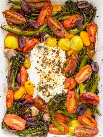 Cherry tomatoes, broccolini, olives, garlic and goats cheese after being in the oven