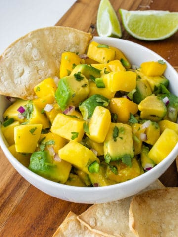 Mango avocado salsa served in a bowl with lime and corn chips