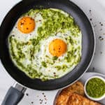 Pesto eggs on a fry pan with a side of toast and extra pesto