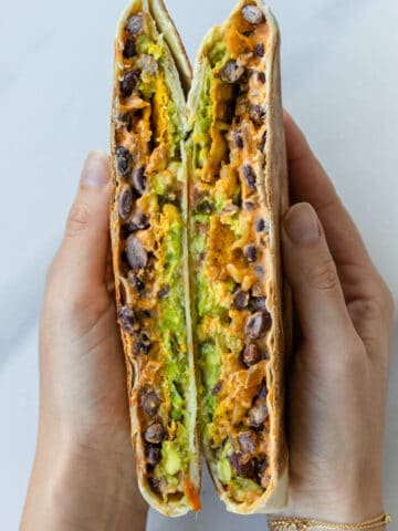 Hands holding homemade crunchwrap in half showing the inside
