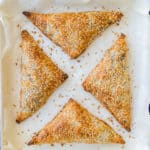 Baked spinach and feta triangles on an oven tray