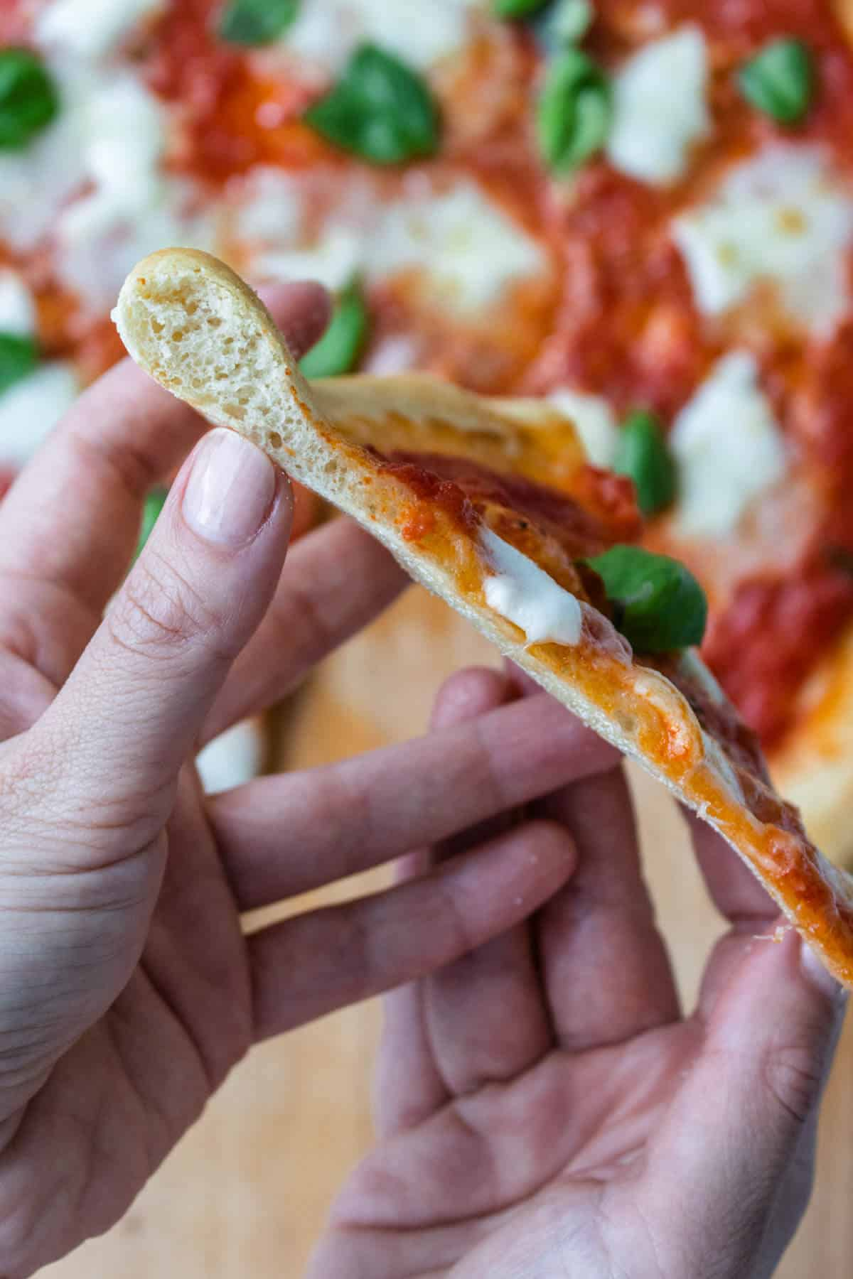 Slice of Italian pizza held on the side to show the crust