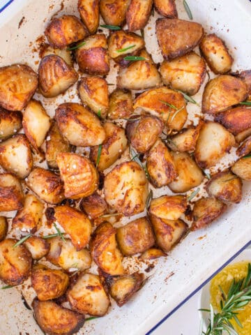 Crispy roasted potatoes recipe in an oven dish with garlic oil on the side