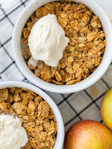 Ramekins of healthy apple crumble topped with a scoop of ice cream