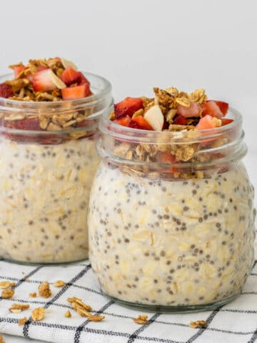 Easy overnight oats in glass jars topped with granola and strawberries