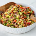 Quinoa salad served in a bowl with mixing spoons
